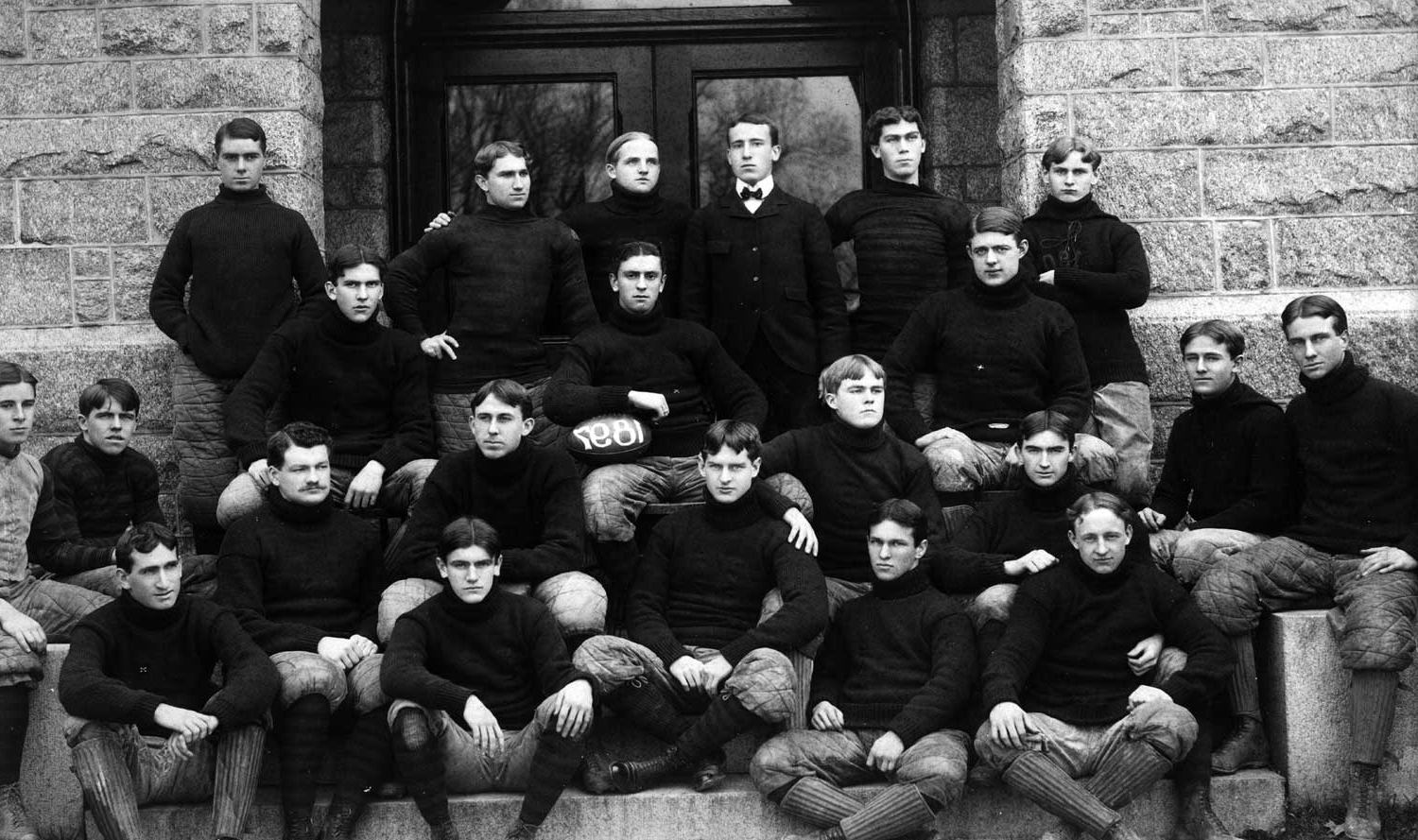 the football team poses together back in the late 1800s