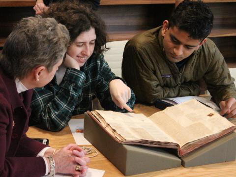 students and a faculty member looking at a rare book from Quaker and 特藏