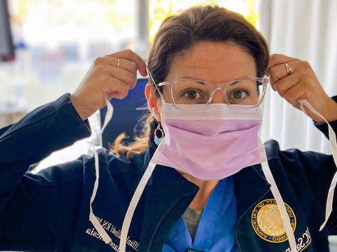 Nurse Tiffani Zalinski wears scrubs and puts on her surgical mask