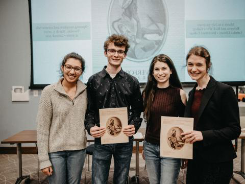 a photo of Sarah Watson and three student curators smiling and holding up the catalog of the Crossing Borders exhibit