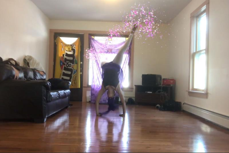 A woman doing a handstand with pink sparkles animated on top of her movement