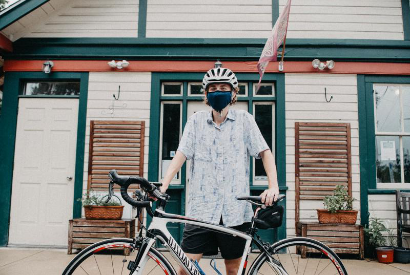 Matthew Katz '22 wears a bike helmet and mask, st和ing with his bicycle in front of one of the vintage train stations on the Main Line